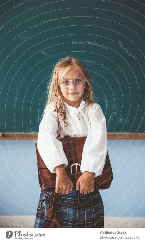 Schüler an der Tafel mit Aktentasche in der Hand Mädchen Klassenraum stehen heiter Glück Buch Kreide niedlich Bildung Schule Schulklasse Jugendliche lernen Kind