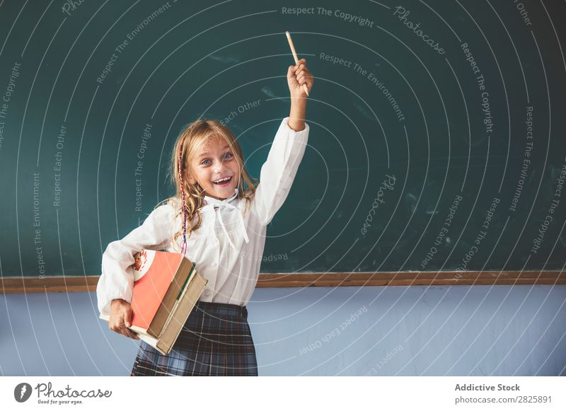 Schüler an der Tafel mit erhobener Hand Mädchen Klassenraum stehen heiter Glück Lächeln Buch Kreide hochreichen niedlich Bildung Schule Schulklasse Jugendliche