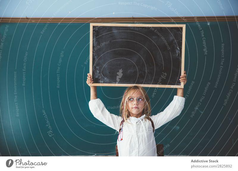 Glückliches Mädchen stehend mit Tafel Klassenraum Halt schreien über Kopf heiter niedlich Bildung Schule Schulklasse Schüler Jugendliche lernen Kind