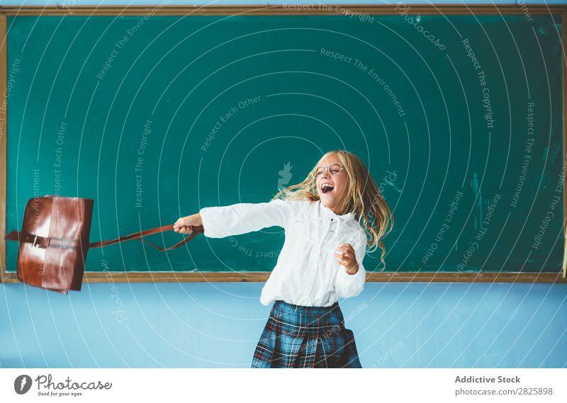 Mädchen wirft Rucksack im Klassenzimmer. Klassenraum Tafel Freude Werfen Ferien & Urlaub & Reisen Glück heiter stehen niedlich Bildung Schule Schulklasse
