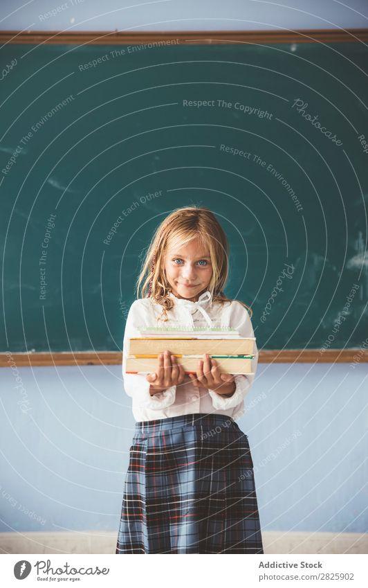 Schüler an der Tafel mit Büchern in der Hand Mädchen Klassenraum stehen heiter Glück Lächeln Buch Kreide niedlich Bildung Schule Schulklasse Jugendliche lernen