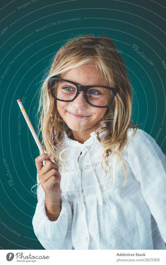 Niedliches Schulmädchen mit Bleistift Mädchen Klassenraum Tafel Brillenträger Lächeln heiter stehen niedlich Bildung Schule Schulklasse Schüler Jugendliche