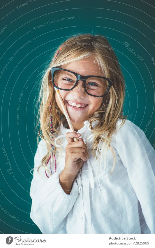 Niedliches Schulmädchen mit Bleistift Mädchen Klassenraum Tafel Brillenträger Blick in die Kamera Lächeln heiter stehen niedlich Bildung Schule Schulklasse