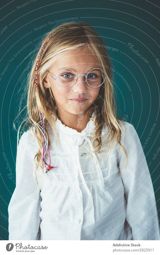 Niedliche Schülerin, die in einem Klassenzimmer posiert. Mädchen Klassenraum Tafel Brillenträger heiter stehen niedlich Bildung Schule Schulklasse Jugendliche