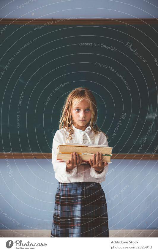 Schüler an der Tafel mit Büchern in der Hand Mädchen Klassenraum stehen heiter Glück Buch Kreide niedlich Bildung Schule Schulklasse Jugendliche lernen Kind