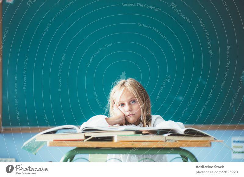 Gelanges Mädchen im Klassenzimmer Klassenraum Tafel sitzen Schreibtisch Blick in die Kamera gelangweilt matt träumen niedlich Bildung Schule Schulklasse Schüler