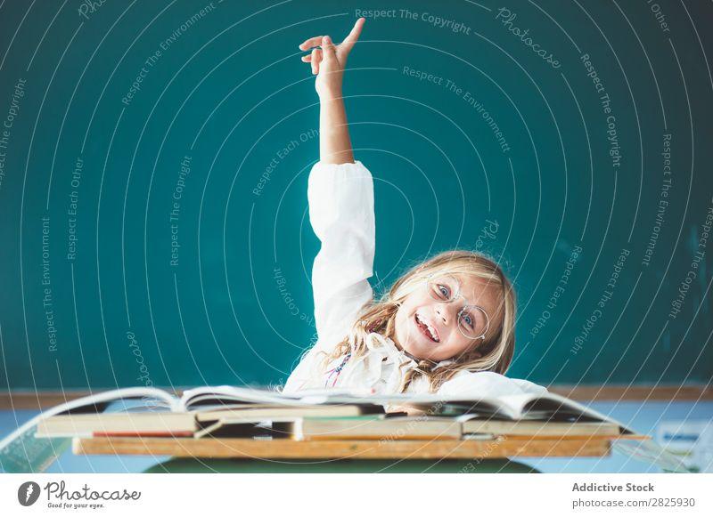 Fröhliches Schulmädchen mit erhobener Hand Mädchen Klassenraum Tafel sitzen Schreibtisch Lächeln Glück hochreichen Antwort niedlich Bildung Schule Schulklasse