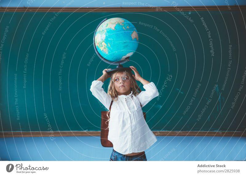 Schülermädchen posiert mit Globus Mädchen Klassenraum Geografie niedlich Bildung Schule Schulklasse Jugendliche lernen Kind Schulunterricht Pupille Wissen