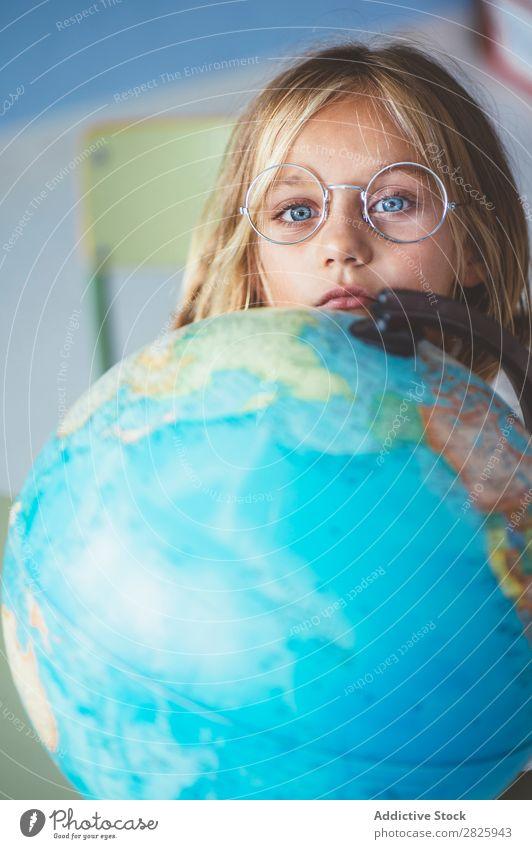Schülermädchen zeigt auf den Globus Mädchen Klassenraum sitzen Geografie zeigen niedlich Bildung Schule Schulklasse Jugendliche lernen Kind Schulunterricht