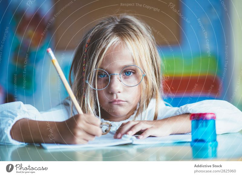 Nachdenkliches Mädchen beim Schreiben im Unterricht Klassenraum sitzen Schreibtisch schreibend Bleistift Zeichnung Denken Fürsorge gelangweilt niedlich Bildung