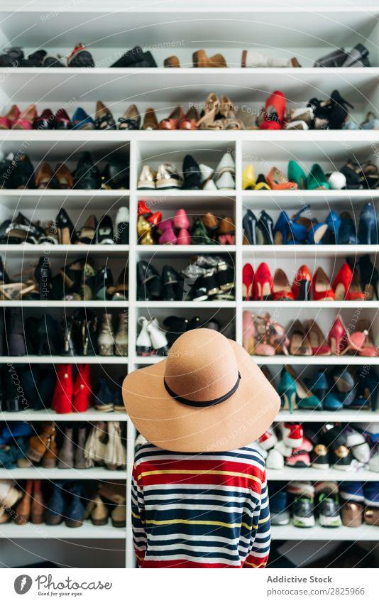 Person vor den Regalen mit verschiedenen Schuhen Mensch Rückansicht anonym unkenntlich Hut Ablage Schrank Mode Lager Stil Kleiderschrank Bekleidung heimwärts