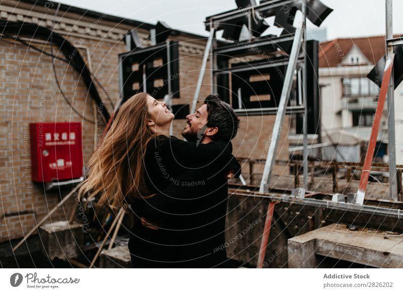 Ein Paar umarmt sich gegenseitig auf dem Dach. Umarmen Dachterrasse heiter Großstadt Hinweisschild Liebe sitzen Skyline Architektur Liebesgeschichte Stadt