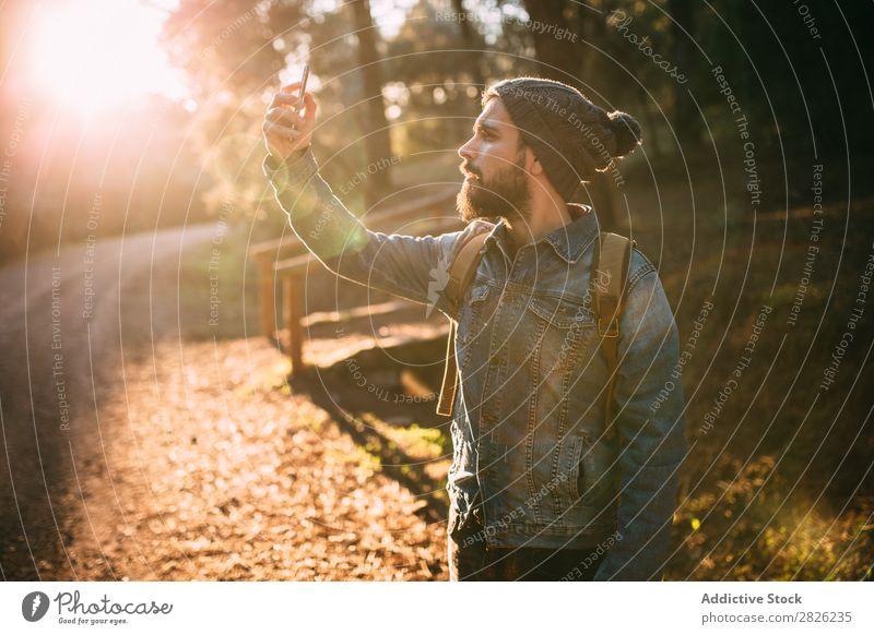 Mann mit Selfie auf sonniger Herbststraße Tourist Wald Porträt Rucksack Telefon Straße