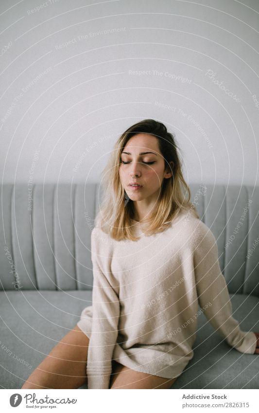Verschlafene Frau auf der Couch schläfrig Augen geschlossen Liege Sofa Sitzen Porträt bequem jung heimwärts besinnlich nachdenklich attraktiv schön Raum