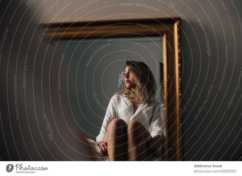 Das Spiegelbild einer Frau, die ihre Knie umarmt und auf einem Bett sitzt. Horizontale Innenaufnahme. umarmend Reflexion & Spiegelung Wegsehen Morgen heimwärts
