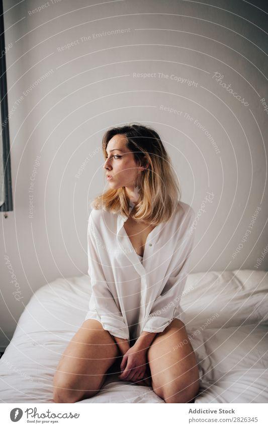 Junge Frau sitzt auf einem Bett in weißer Unterwäsche und schaut weg. Morgen Wegsehen heimwärts attraktiv schön aussruhen Lifestyle Person Sitzen Schlafzimmer