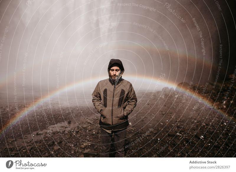 Mann, der auf dem Hintergrund des Wasserfalls posiert. Regenbogen Island strömen Nebel Tourismus Berge u. Gebirge natürlich Ferien & Urlaub & Reisen Landschaft