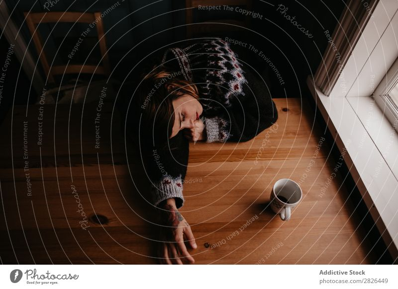Frau auf dem Tisch liegend mit Tasse schlafen Island heimwärts Morgen erschöpft Müdigkeit träumen schlafend Stress Erholung Innenaufnahme aussruhen Becher
