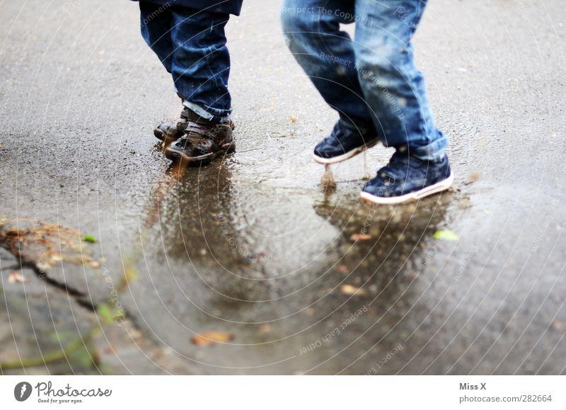 Herbstspaß Mensch Kind Wasser Freude kalt Gefühle springen Beine Fuß Kindheit dreckig nass Jeanshose Bürgersteig Kleinkind Lebensfreude