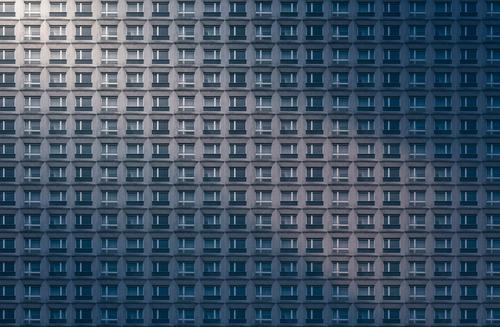 architektonisches Muster, Betonfassade eines miserablen Wolkenkratzers Fassade Konformität Anonymität Hintergrund übergangslos Wiederholung Megastadt anonym