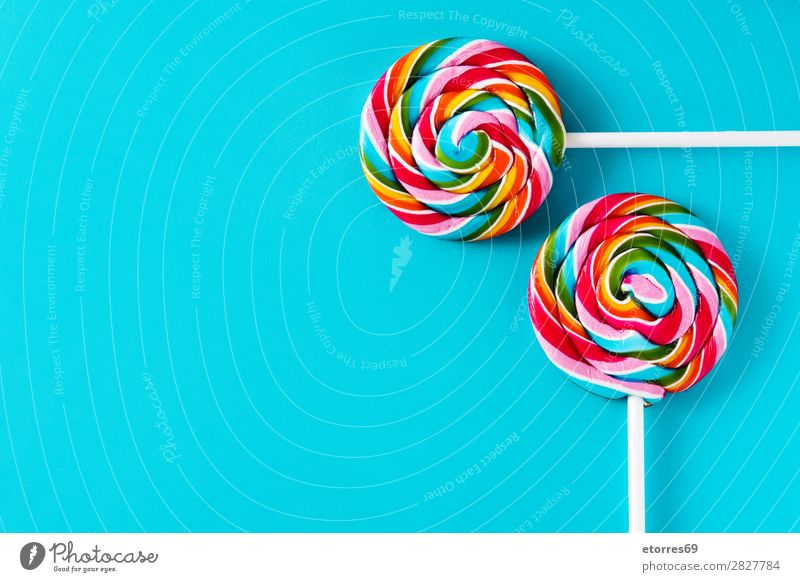 Bunte Lollis auf blauem Hintergrund. Draufsicht. Kopierbereich Lollipop Farbe mehrfarbig Zucker Süßwaren Bonbon süß geschmackvoll Textfreiraum Lebensmittel