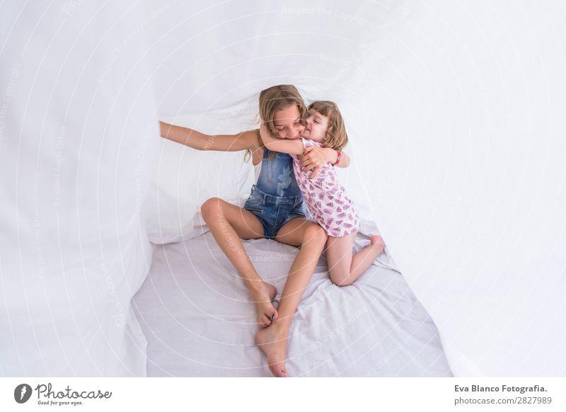 Zwei schöne Schwesternkinder, die unter weißen Laken spielen. Lifestyle Freude Glück Freizeit & Hobby Spielen lesen Sommer Schlafzimmer Kind Mensch feminin Baby