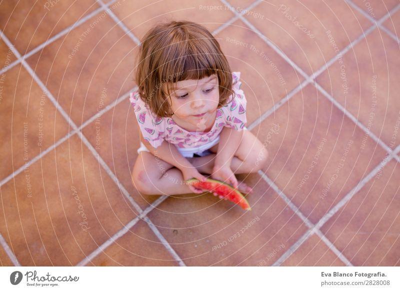 Draufsicht auf ein schönes Kind Mädchen beim Essen von Wassermelone Frucht Speiseeis Freude Glück Ferien & Urlaub & Reisen Sommer Haus Garten feminin Baby