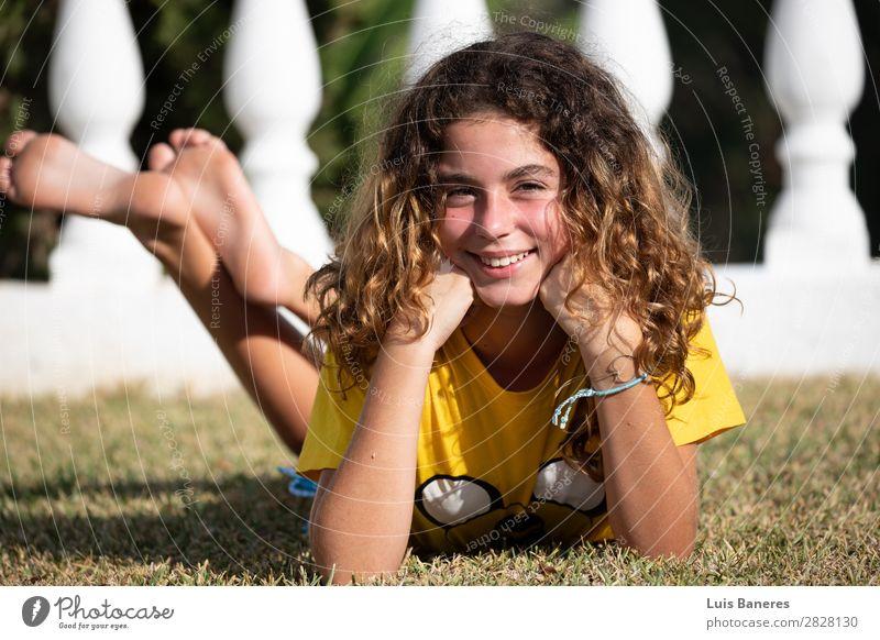 liegend und spielend mit ihren Beinen Freude Glück schön Gesicht Sommer Sonne Garten Erfolg Mensch Frau Erwachsene Natur Gras T-Shirt blond Lächeln lachen