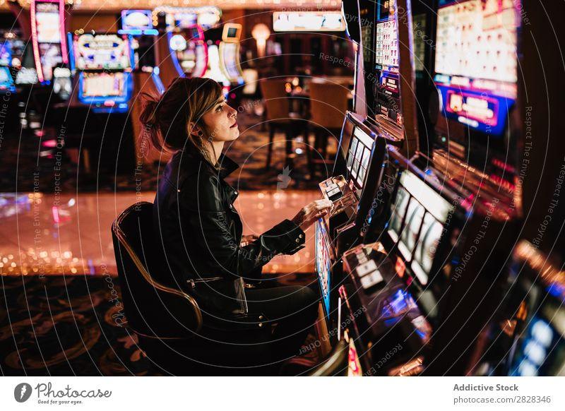 Frau spielt Spielautomat Glücksspiel Kurhaus Spielen Risiko Spieler Erfolg Glücksspieler glücklich Nachtleben Vermögen Aufregung Gelegenheit Nachtclub Vegas