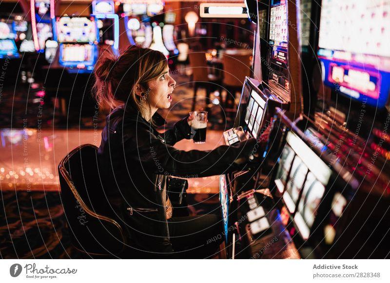 Seitenansicht einer Frau, die im Casino sitzt und am Spielautomaten spielt. Glücksspiel Kurhaus Risiko Spieler Gewinner Spielen Glücksspieler glücklich