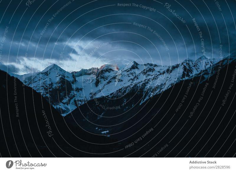 Verschneite Berge unter starkem Himmel Natur Winter Berge u. Gebirge Wolken schwer Landschaft Schnee Ferien & Urlaub & Reisen Eis schön weiß Jahreszeiten kalt
