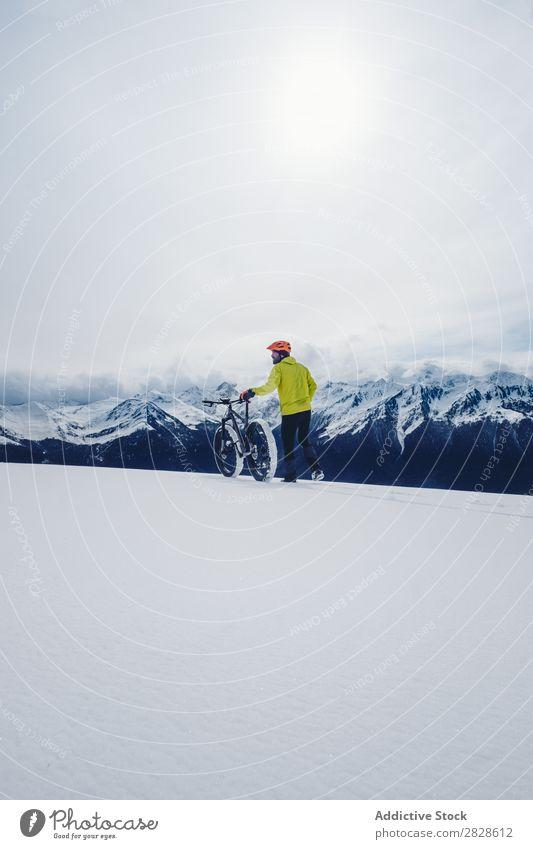 Sportler mit Fahrrad in den Winterbergen Tourist laufen Berge u. Gebirge professionell gefroren