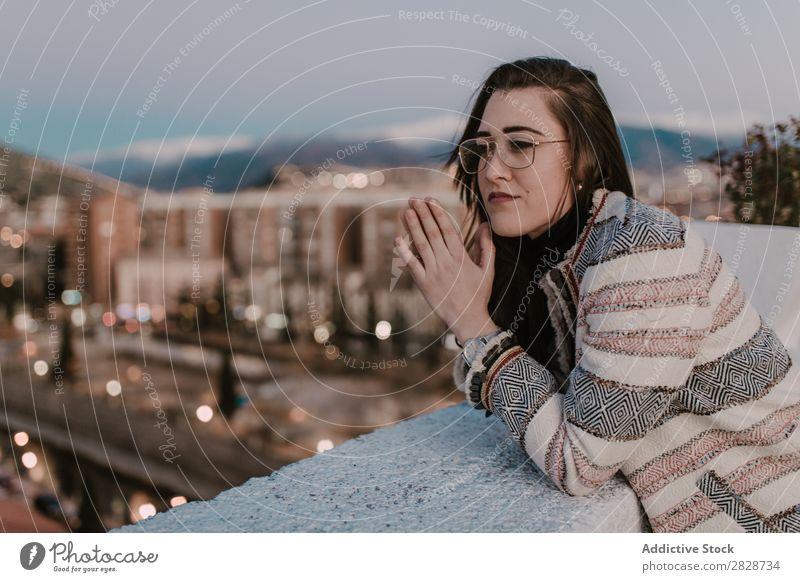 Fröhliche junge Frau, die sich auf den Zaun lehnt. hübsch Jugendliche schön anlehnen Stadt Straße heiter Lächeln Brillenträger brünett attraktiv Mensch