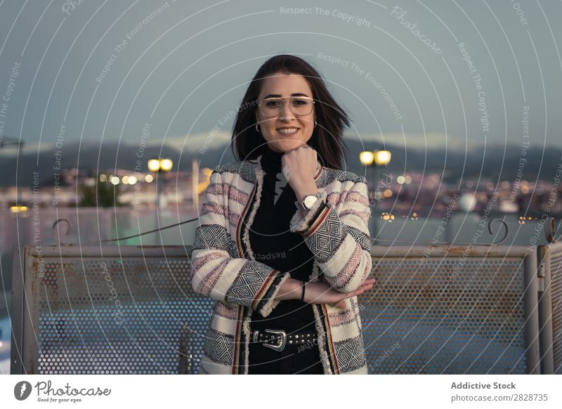 Fröhliche junge Frau, die in die Kamera schaut. hübsch Jugendliche schön Zaun anlehnen Stadt Straße heiter Lächeln Brillenträger brünett attraktiv Mensch