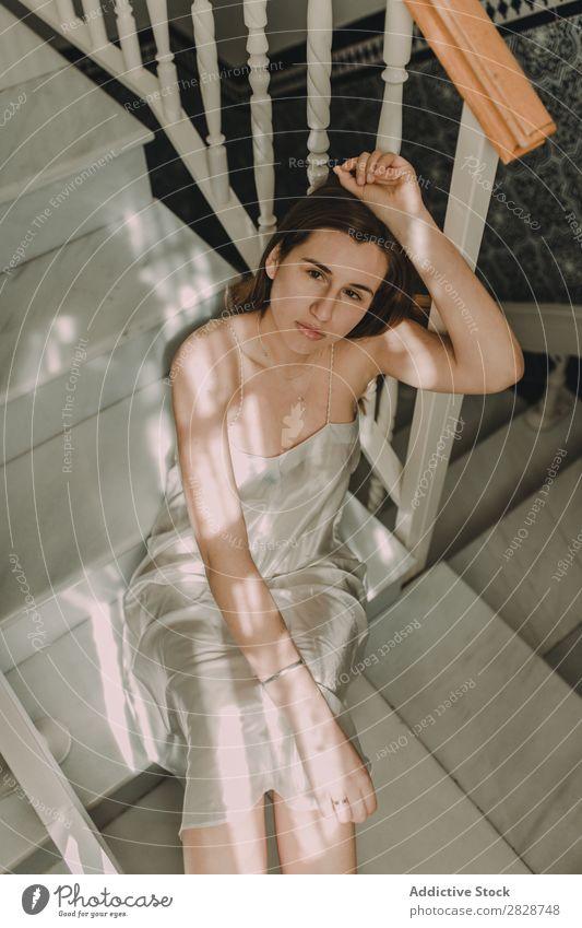 Junge sinnliche Frau, die auf der Treppe sitzt. hübsch Jugendliche schön Foyer Freitreppe sitzen aufschauend brünett attraktiv Mensch Beautyfotografie