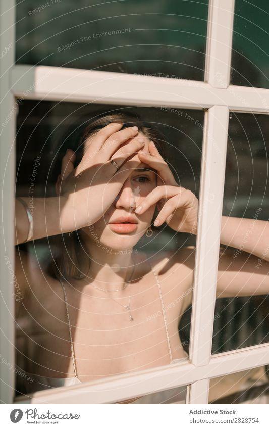 Frau berührt Gesicht am Fenster hübsch Jugendliche schön Fürsorge besinnlich Denken Wegsehen schockiert berührendes Gesicht brünett attraktiv Mensch