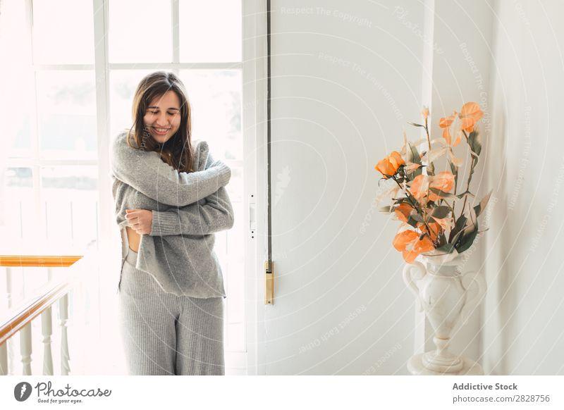 Frau beim Ausziehen zu Hause hübsch Jugendliche schön strecken Augen geschlossen grau Bekleidung abfliegend brünett attraktiv Mensch Beautyfotografie Erwachsene