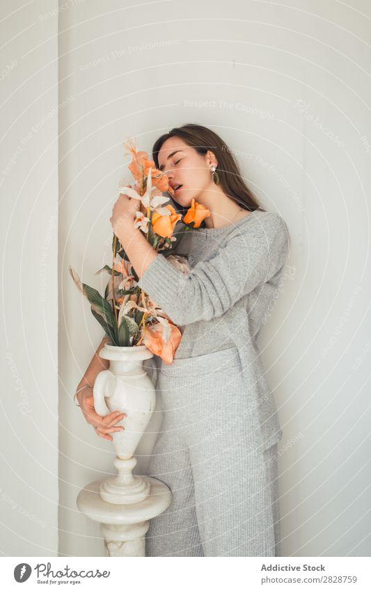 Sinnliche Frau, die Blumen umarmt. hübsch Jugendliche schön umarmend Orange Vase stehen genießen Augen geschlossen brünett attraktiv Mensch Beautyfotografie