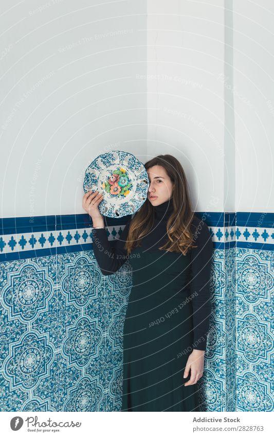 Stehende Frau mit farbigem Teller hübsch Jugendliche schön stehen Wand Fliesen u. Kacheln blau Speise Körperhaltung Foyer brünett attraktiv Mensch