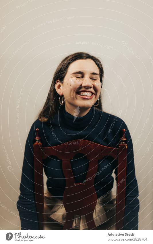 Lächelnde Frau auf dem Stuhl sitzend hübsch Jugendliche schön heiter Glitzer Gesicht brünett attraktiv Mensch Beautyfotografie Erwachsene Stil niedlich
