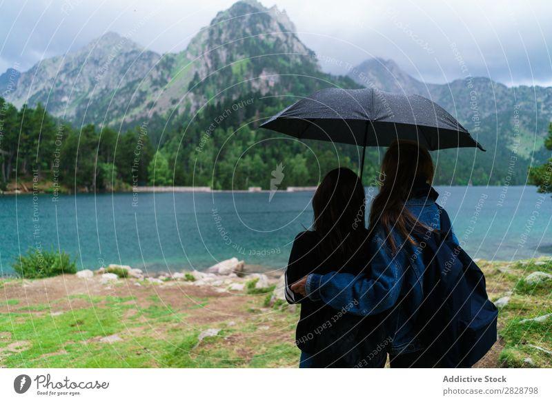 Frauen unter Schirm in den Bergen Berge u. Gebirge Zusammensein stehen wandern See Wasser Regenschirm