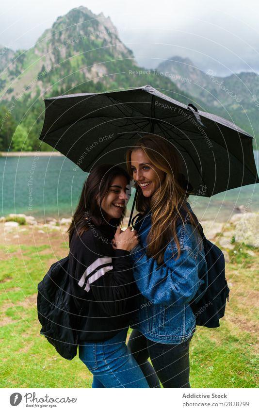 Frauen unter Schirm in den Bergen Berge u. Gebirge Zusammensein stehen Lächeln wandern See Wasser