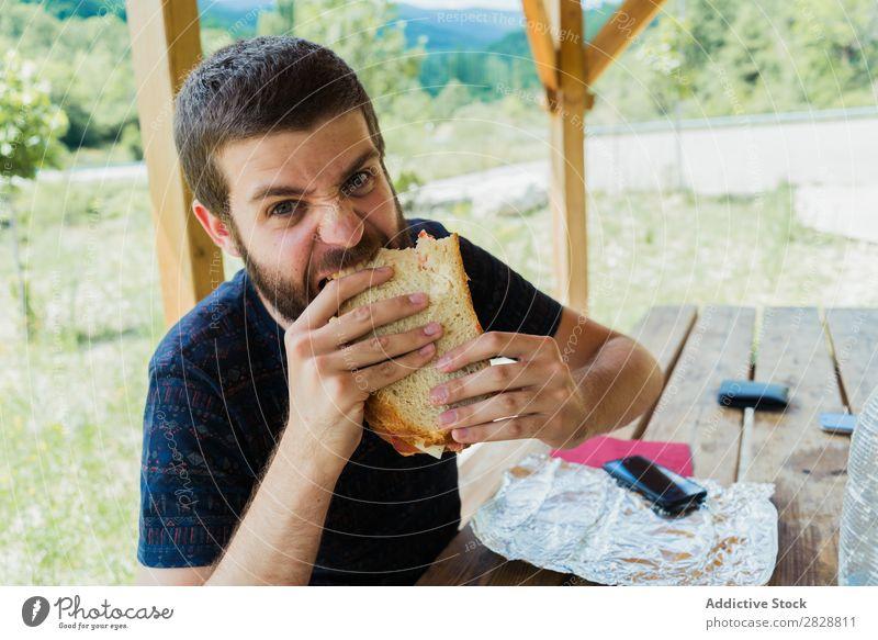 Ausdrucksstarker Mann mit Sandwich Essen Wut so tun, als ob Spaß haben Appetit & Hunger expressiv verrückt Körperhaltung Gesichtsbehandlung Verstand spielerisch
