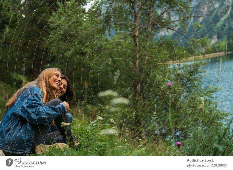 Fröhliche Frauen am See sitzend Berge u. Gebirge Lächeln heiter Zusammensein Glück lachen wandern Wasser umarmend Ferien & Urlaub & Reisen Abenteuer Tourist