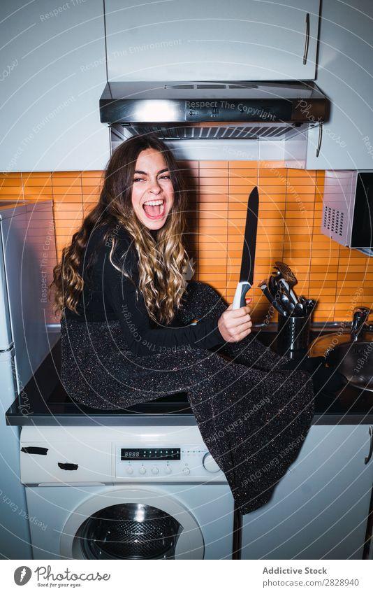 Ausdrucksstarke Frau, die mit dem Messer posiert. hübsch Körperhaltung expressiv sitzen Tisch gefährlich heimwärts Küche schön Lifestyle Jugendliche Mensch