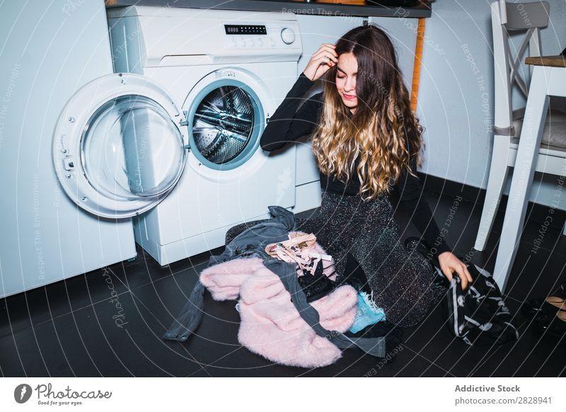 Frau, die an der Waschmaschine sitzt. Körperhaltung heimwärts Wäsche Bekleidung sitzen Küche Lächeln