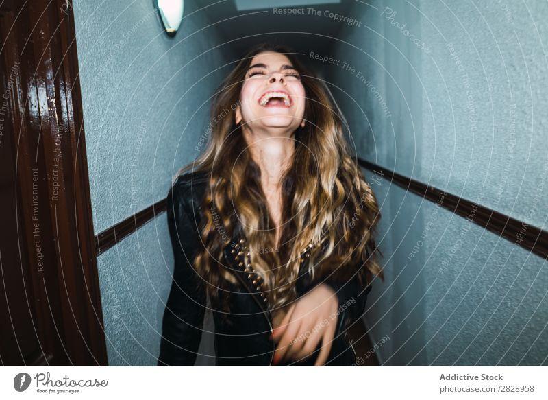 Fröhliche Frau, die in der Halle posiert. Jugendliche attraktiv heimwärts Lächeln heiter Glück Flur Gang expressiv Körperhaltung verführerisch schön Mensch