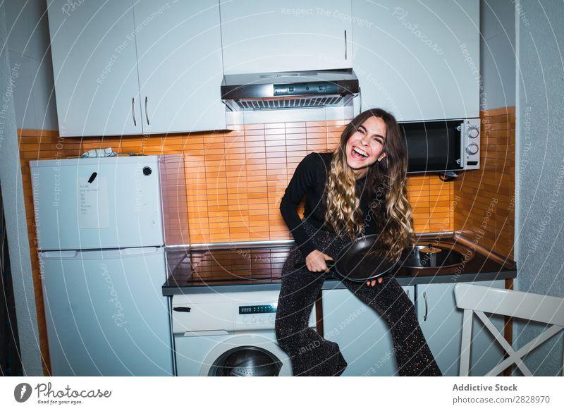 Frau auf Küchentisch mit Pfanne sitzend Körperhaltung heimwärts Tisch Blick in die Kamera schön