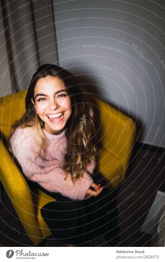 Junge Frau ruht sich auf einem Sessel aus. Jugendliche attraktiv heimwärts Pullover rosa sitzen Glück expressiv Körperhaltung verführerisch schön Mensch hübsch