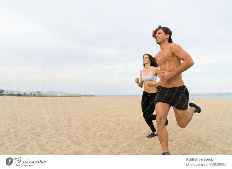 Zwei Sportler beim Laufen am Strand Paar rennen Mensch sportlich Training Küste Aktion Joggen Fitness Läufer Zusammensein Geschwindigkeit Außenaufnahme Bewegung